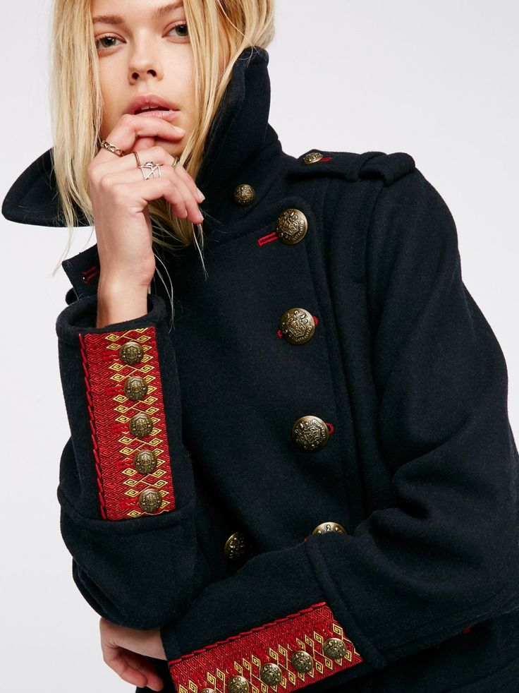 City Limits Peacoat | In a wool-blend this classic style peacoat is in a cropped silhouette with bronzed metal etched buttons and lined hip pockets. Embroidery detailing on the back and sleeve cuffs and contrast red trim throughout. Lined.