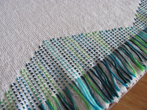 My Little Peacock is a unique Swedish Weave pattern created and made by myself on 100% white cotton monks cloth. I used a variegated acrylic yarn in shades of bright blue and green. I also wanted to create a unique design along the fringe edges at both short edges. All edges are secured by machine sewing. This blanket measures 2-1/2 yards long x 60 inches wide. It can be used for display and/or for cuddling up in. Care: Machine wash cold, gentle. Dry low heat, gentle. Remove damp and hand…