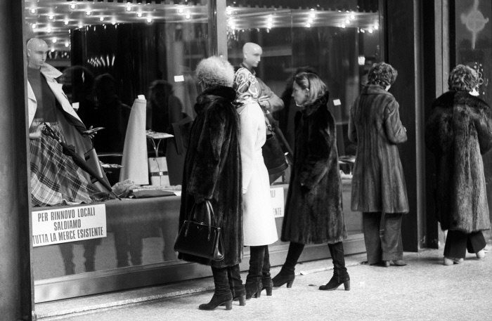 A group of women look at the windows of a clothing store in the days of sales. Italy, seventies MONDADORI PORTFOLIO/Adriano Alecchi