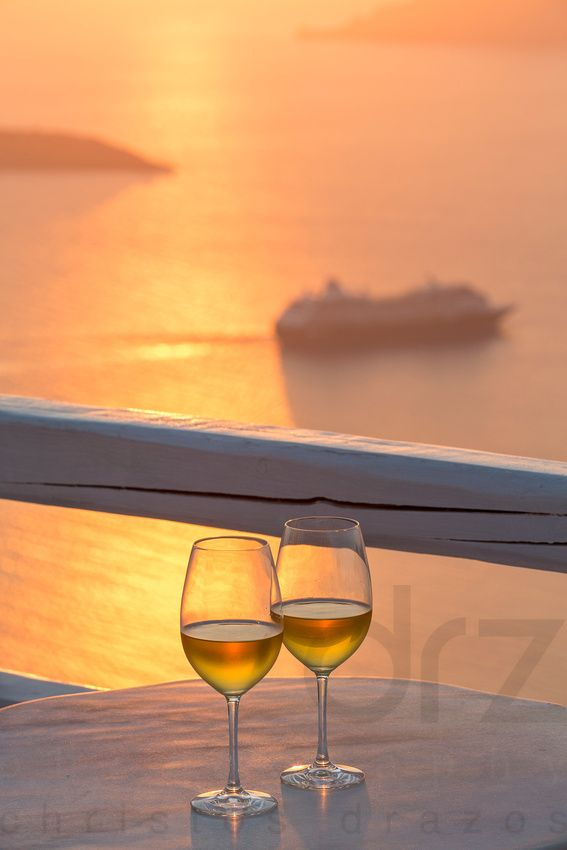 Enjoy the sunset with a glass of rose wine in Santorini, Greece.