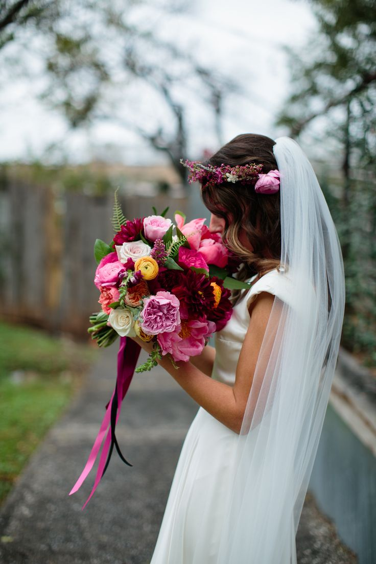 Urban boho chic bride with flower crown and bouquet in berry tones including coral charm peony, garden roses, burgundy dahlia, and ranunculus.  | Gypsy Floral and Events | Paige Newton Photography | Beau tied Events |  #bohobride #berrytones #bouquet #weddingflowers #austinflorist #wedding #bohemian #bohochic #bridalportrait #flowercrown