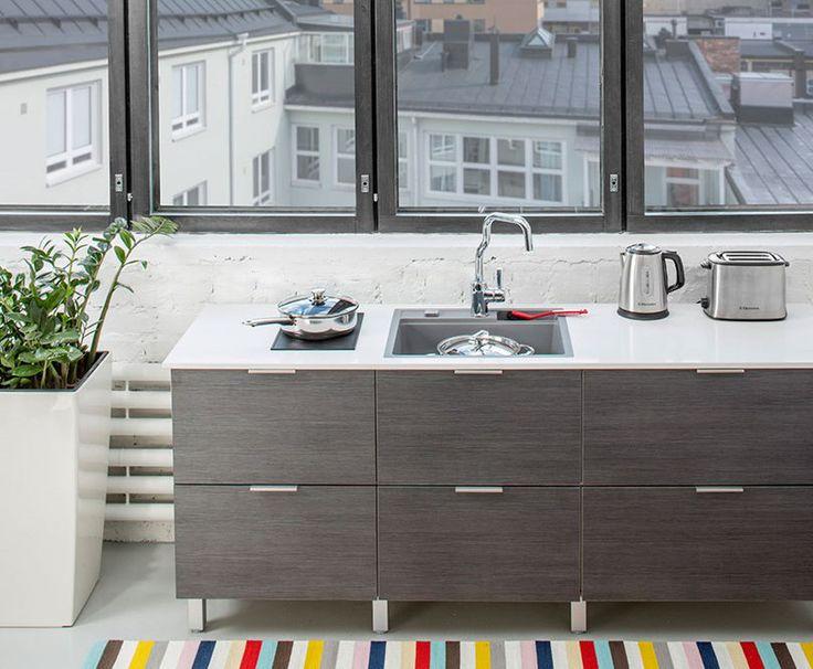 Harmaa komposiittiallas keittiön pöytätasoon asennettuna