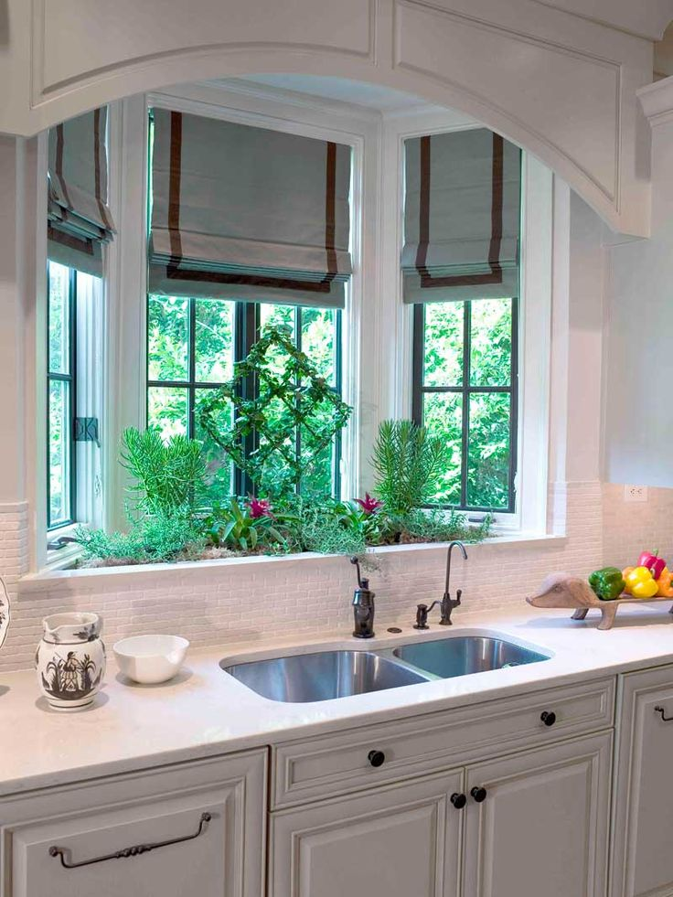 Beautiful Roman Shades enhance this Kitchen's bay window