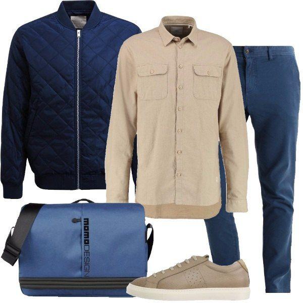 Total look da uomo per tutti i giorni composto da un bomber blu navy, una camicia di cotone beige, un paio di pantaloni blu modello chino, una borsa a tracolla capiente in tessuto tecnico blu e un paio di sneakers in pelle di vitello martellata beige.