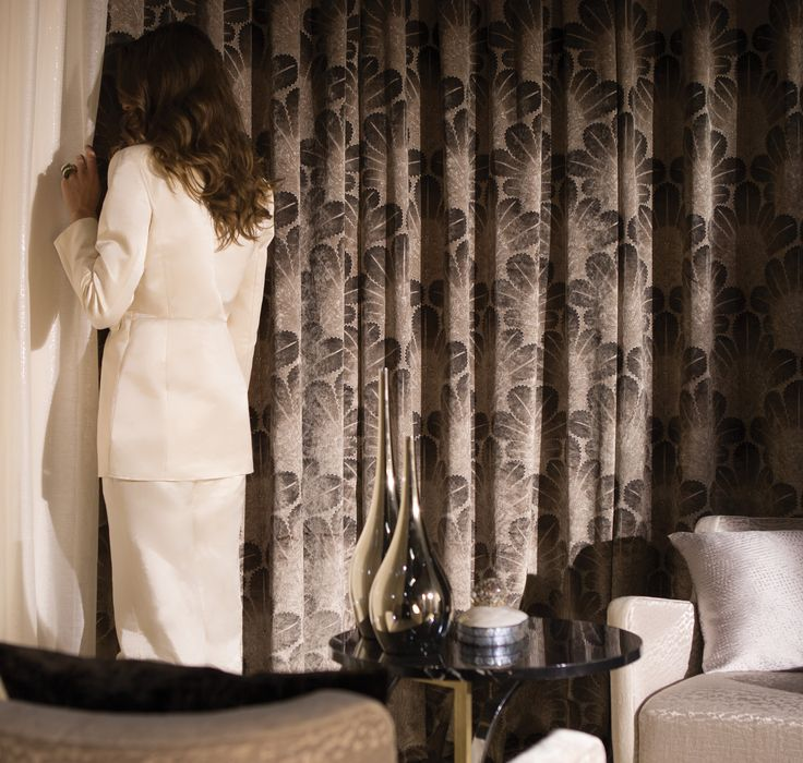 Cushion: ESQUISSE AU MUR, M111403, Textured silk // Model's suit: BAHAMA VILLAGE, M105602, Linen & cotton sateen Curtains (from left to right): MARDI DE POESIE, M120302, English gauze / PALMETTE ART, M118204, Printed velvet