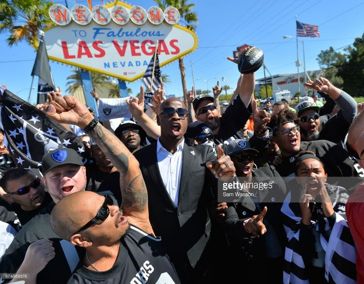 Former Oakland Raiders player Akbar Gbaja-Biamila (center) leads Oakland Raiders fans in a cheer during the team's 2017 NFL Draft event at the Welcome to Fabulous Las Vegas sign on April 29, 2017 in Las Vegas, Nevada. National Football League owners voted in March to approve the team's application to relocate to Las Vegas. The Raiders are expected to begin play no later than 2020 in a planned 65,000-seat domed stadium to be built in Las Vegas at a cost of about USD 1.9 billion.