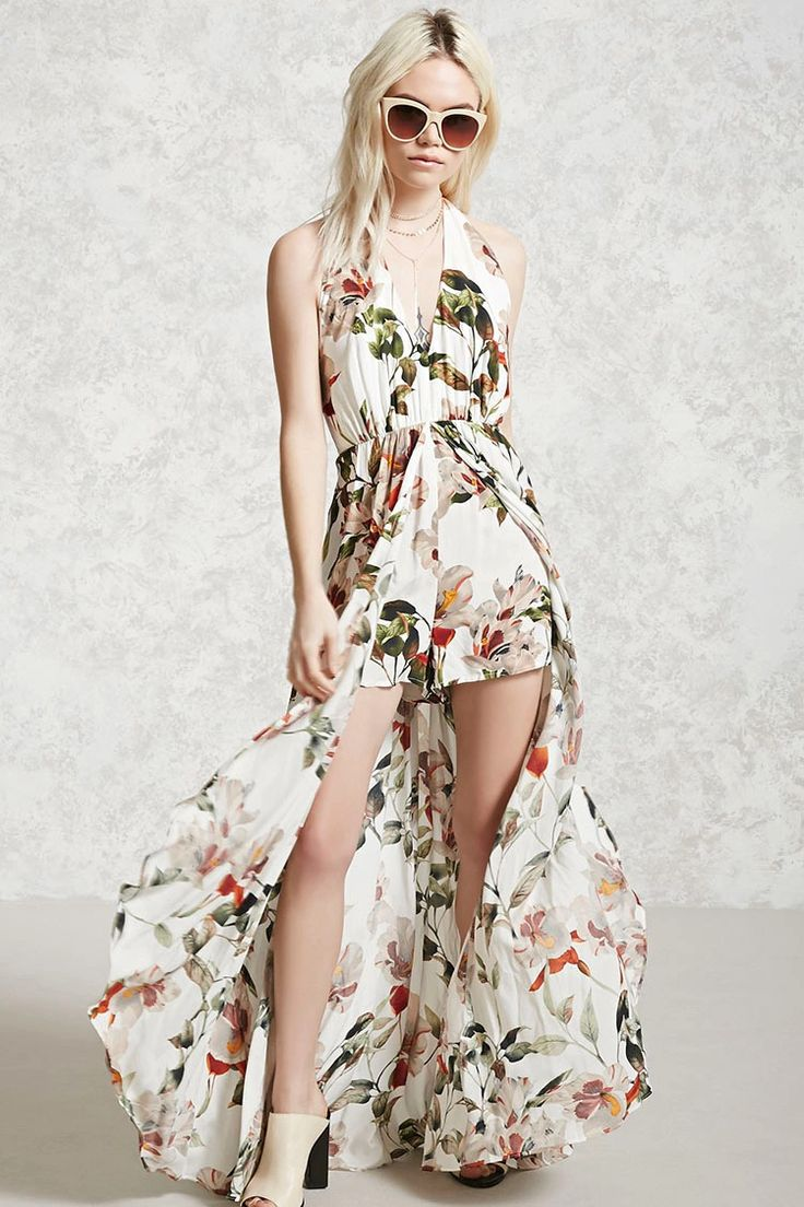 A woven skort romper featuring an allover floral pattern, a halter V-neckline with dual button back closures, an elasticized waist, a maxi skirt overlay, and an open back.