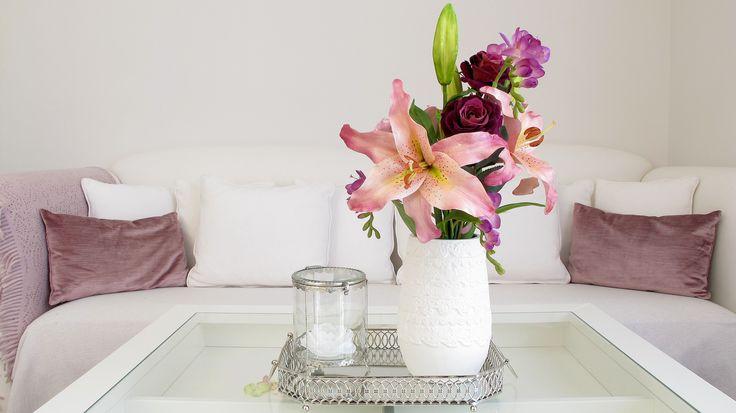 Nidito: bandeja metálica con espejo, bote decorativo de vidrio con perfil plateado y vela con forma de flor, todo ello de Zara Home; Jarrón y flores en tonos malvas y rosados de Sia Collections.