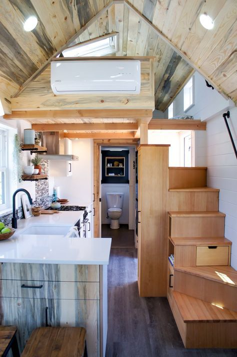 Love the style in this tiny house! Beetle kill pine and gray flooring. White cabinets.