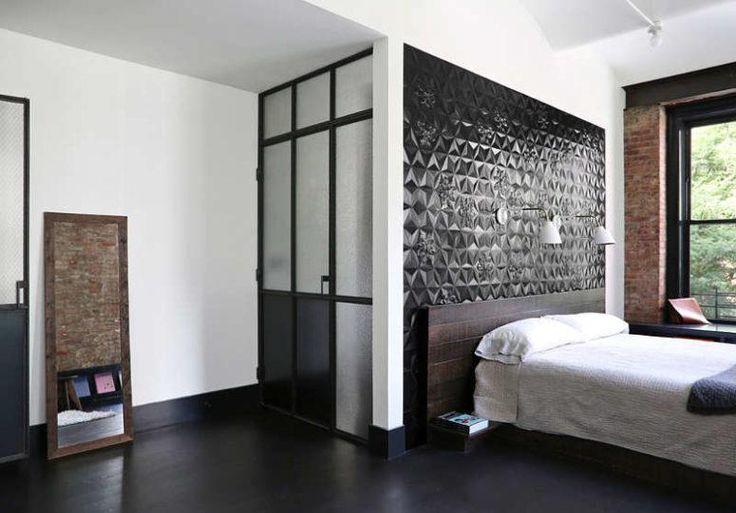 Das Hauptschlafzimmer verfügt über eine schwarze Fliesenaussage Wand und ausgesetzt Ziegel