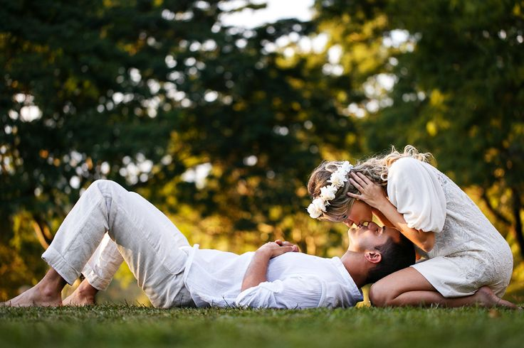 Foto de casal apaixonado se beijando deitados na grama no parque