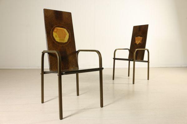 Coppia di sedie con braccioli e schienale alto; legno impiallacciato radica, decoro grafico ad intarsio, metallo brunito. Buone condizioni, presentano piccoli segni di usura. Altezza seduta: 44