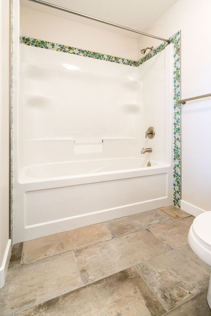 Upstairs Bathtub With A Fun Mosaic Tile Detail Around The Edge