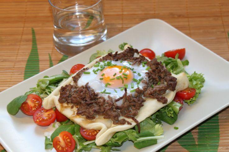 Coupez la pâte à pizza en quatre. Sur chaque part, répartissez le fromage blanc et le bleu. Dans une poêle huilée, faites revenir juste 2 minutes le boeuf avec la coupelle de coeur de bouillon. Répartissez le boeuf sur les pizzetas, cassez un oeuf dessus et faites cuire en bas de four environ 13 à 14 minutes à Th.7/8 (220°C). Saupoudrez de ciboulette et servez sur la salade agrémentée de tomates cerise coupées en deux.