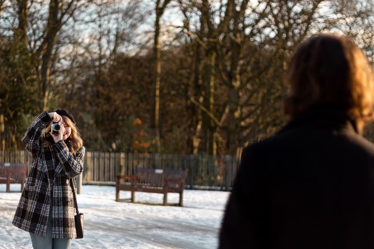 Couples Goals! Winter Engagament shoot in Sefton Park, Liverpool. A girl takes a photograph of her fiancee with her new camera wearing a winter coat in the snow – Folkstar Photography