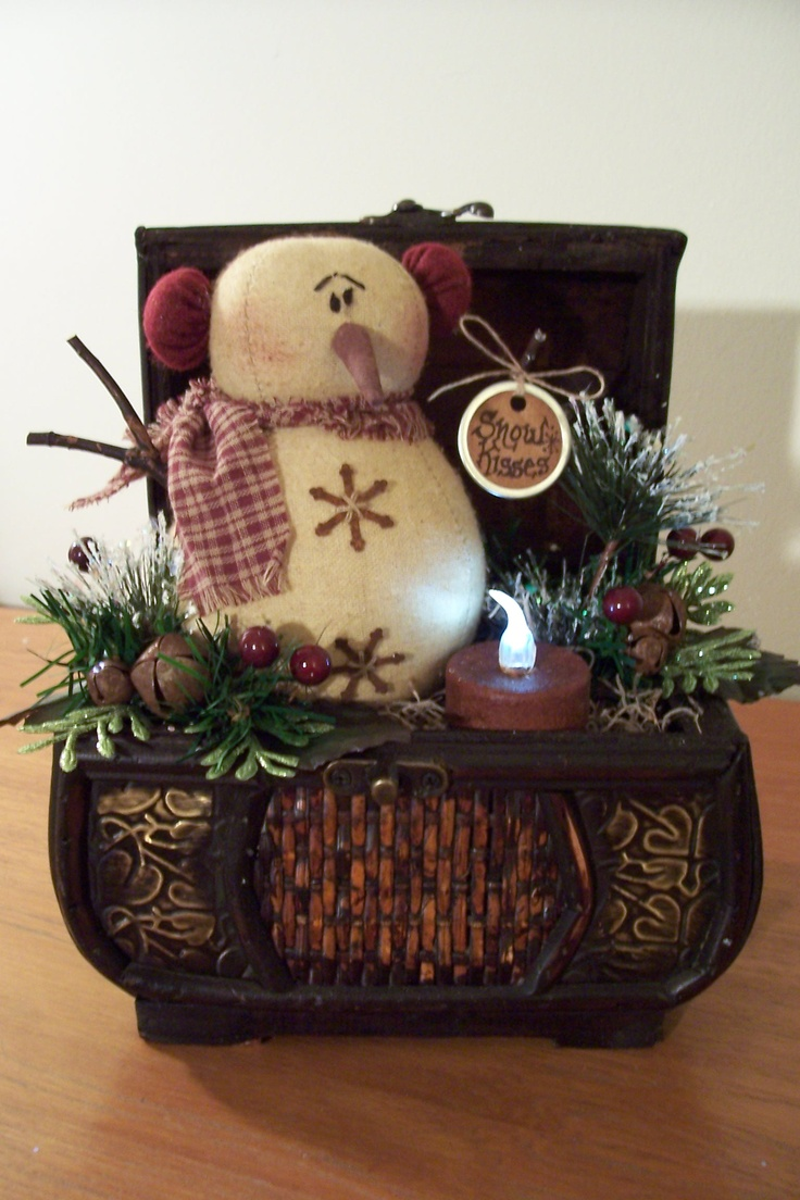 Repurposed Vintage Chest with a cute snowman, sprigs of pine, burgundy berries, frosted ming pine, glittery fern leaves, rusty jingle bells, grungy cinnamon rolled tea lite and a prim stained tag that says 'Snow Kisses'.  $18
