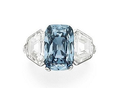 An Exceptional Fancy Blue Diamond ring. Set with a round-cornered rectangular-cut fancy vivid blue diamond, weighing approximately 3.43 carats, flanked on either side by a cut-cornered trapeze-cut diamond, mounted in platinum.