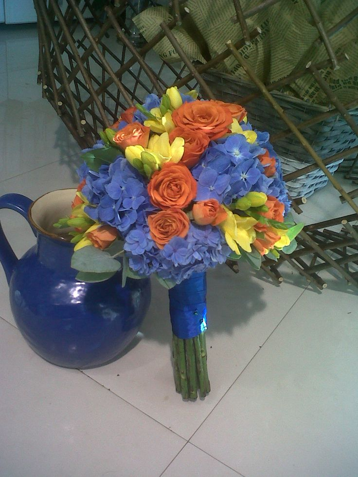 Bridal bouquet made with blue hydrangea,yellow freesia and orange minirosa
