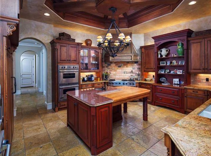 Mediterranean Kitchen with double-L island: one L is granite-topped cabinetry, the other L is wood chopping block with knee space for barstools... Also note the big hutch wall...