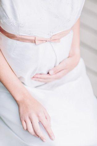 noni noni Brautkleider 2015 | schwangere Braut mit Brautkleid mit Babybauch, zarter Bestickung und rosa Band unter der Brust  (www.noni-mode.de - Foto: Le Hai Linh)