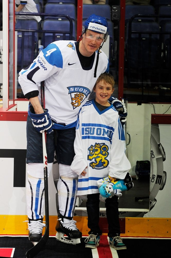 HELSINKI, FINLAND - MAY 11: Finlands Ossi Vaananen #4 poses with a young fan during preliminary round action at the 2013 IIHF Ice Hockey World Championship. (Photo by Richard Wolowicz/HHOF-IIHF Images)