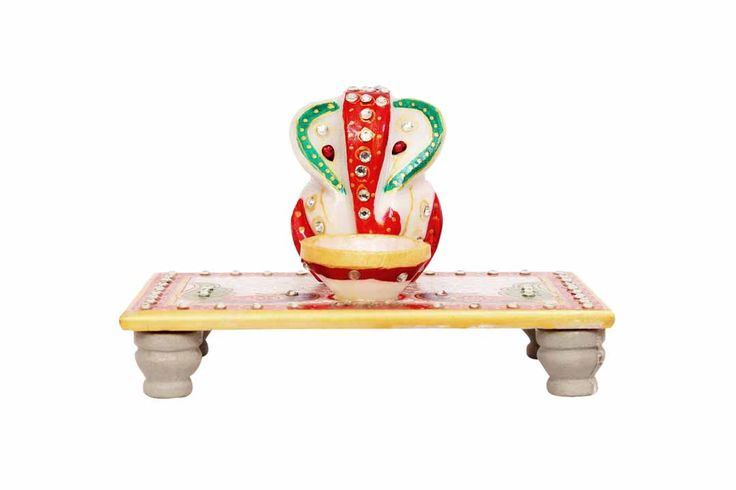 Marble idol of Lord Ganesh adorned in Red, Golden , Green and Peacock Blue artwork. This aethestically done Ganesh chowki comes with a Marble diya, tinted in a similar manner. Will usher in a pious ambience to your surroundings.