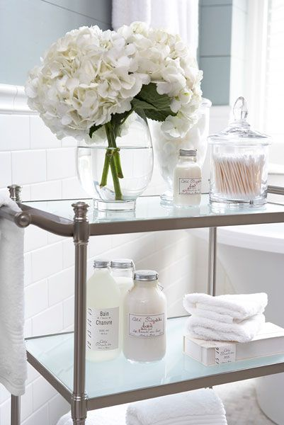 Love the FRESH WHITE FLOWERS to brighten it up...also the use of clean glass containers for STUFF...