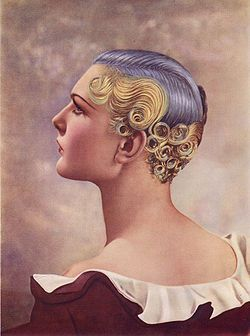 First Prize won at the Hairdressing Fashion Show London, 1935, using an Icall permanent-waving machine. The hair is shorter even than in the 1920s and curls/waves are restricted to the back and sides, revealing the ears and neck. The colors were achieved by adding pigments to the setting lotion.