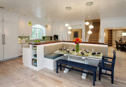 A built-in banquette built against the kitchen island creates a booth-style breakfast area...