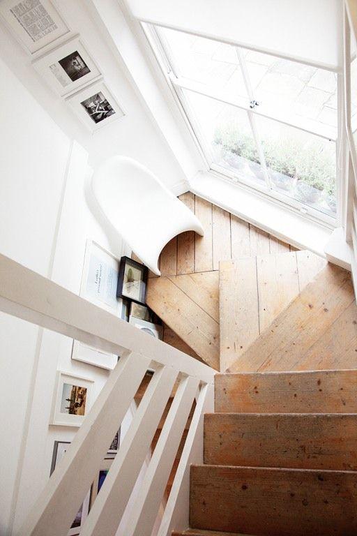 大きな窓のある踊り場に椅子が置かれた遊び心のある階段