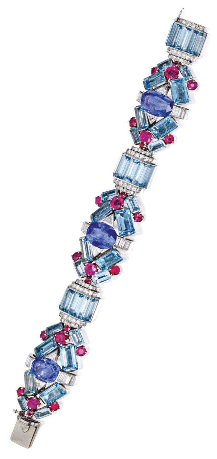 An Art Deco Platinum, Aquamarine, Sapphire, Ruby and Diamond Bracelet, Circa 1935. The highly flexible geometric design set with three cushion-cut sapphires, accented by emerald-cut aquamarines, further set with variously-cut diamonds, completed with round rubies. #ArtDeco #bracelet