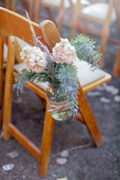 Rustic flowers in mason jars line the chairs on the aisle: http://www.stylemepretty.com/little-black-book-blog/2014/08/26/rustic-hay-ride-wedding-at-rileys-farm/ | Photography: Alders - http://aldersphotography.com/