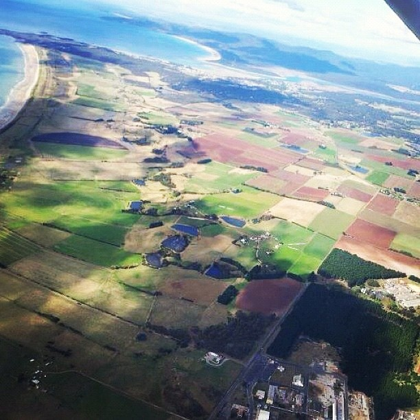 An unusual view of 'patchwork quilt' farmland near the city of Devonport with Shearwater and Hawley Beach sneaking into view in the middle distance. Devonport is the arrival port for the ferry Spirit of Tasmania on its sea journey across from Melbourne.