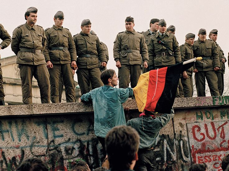East German border guards attempt to stop the first section of the Berlin Wall from being torn down by jubilant crowds in November 1989. One of the protestors is waving a West German flag.