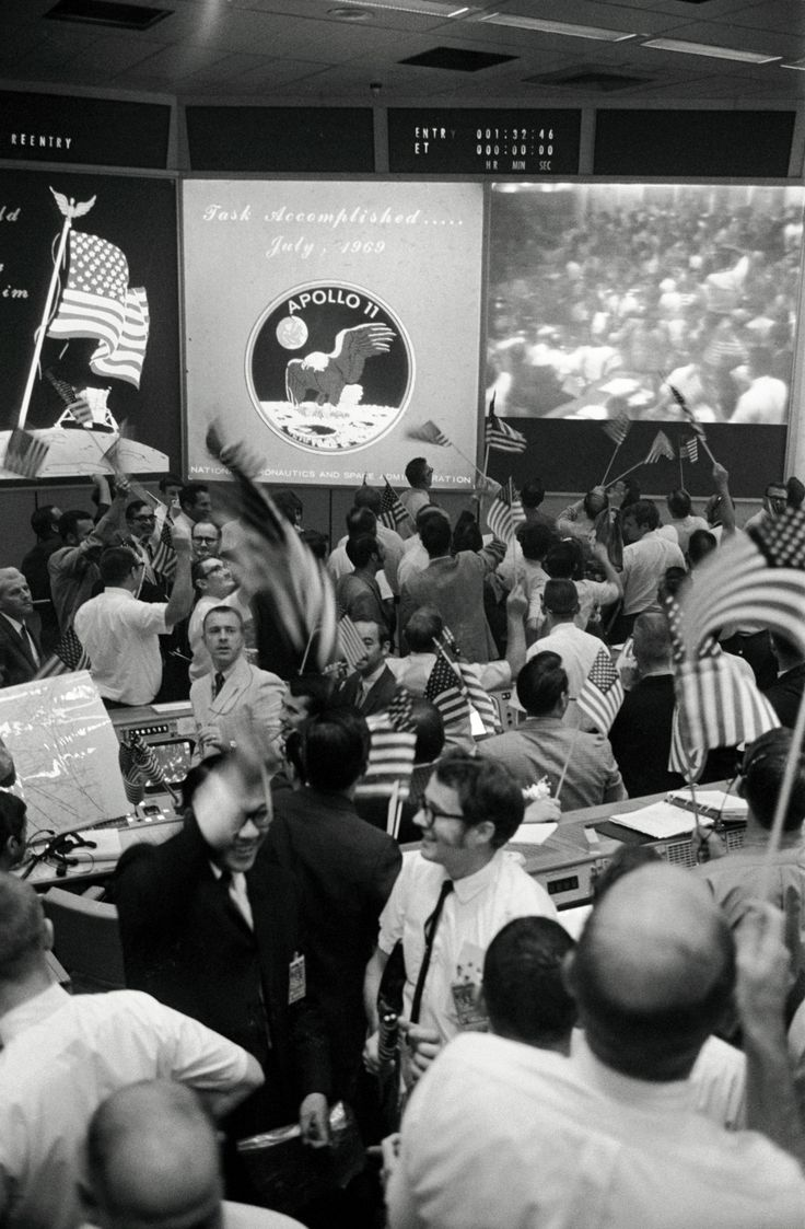 Overall view of the Mission Operations Control Room (MOCR) in the Mission Control Center (MCC), Building 30, Manned Spacecraft Center (MSC), showing the flight controllers celebrating the successful conclusion of the Apollo 11 lunar landing mission.