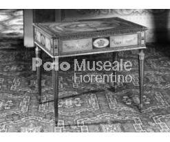 Tavolino neoclassico della fine del '700 notevole per i finissimi intarsi. Oggetti di questo genere sono frequenti nelle descrizioni degli inventari di Palazzo Pitti della fine del '700, questo esemplare però non è rintracciabile negli inventari prima del 1829 non essendo segnalato il vecchio numero.