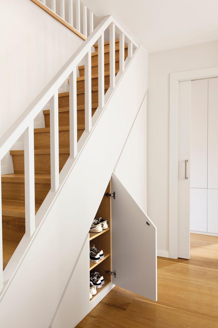 Escalera con peldaños de madera y barandilla blanca aprovechada su estructura con un armario zapatero_00447050