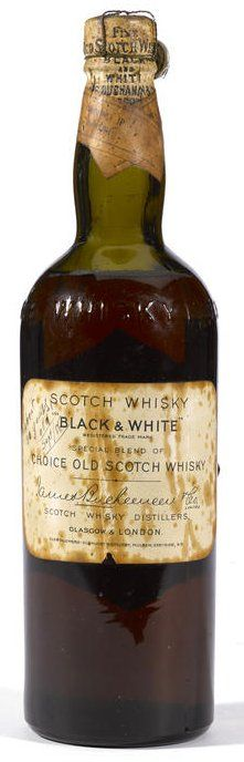 """Black & White James Buchanan & Co. Circa 1928. Driven cork. Capsule wrapped in wire cage with pull-tab embossed with """"Imposta Spiriti"""". Some blotching on label and a small nick on bottom center on label. Hand writing on upper left. Level: Mid shoulder. 4/5 Quart."""