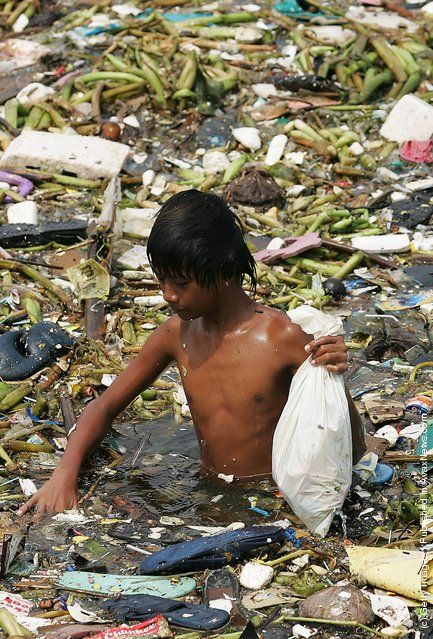 A Philippine boy picks plastic waste from floating rubbish on the water near the Roxas Boulevard along the Manila Bay