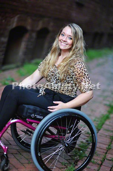 Young woman in a wheelchair in a garden lane way. >>> See it. Believe it. Do it. Watch thousands of spinal cord injury videos at SPINALpedia.com