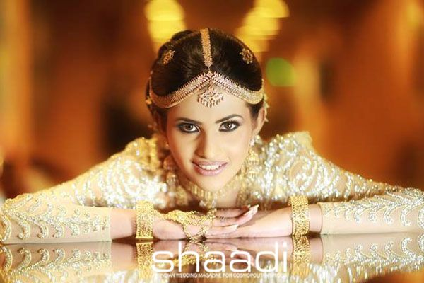 Stunningly dressed in a nude-colored, heavily embellished dress, accentuated with traditional Kandyan jewelry comprising of an elaborate matha-patti, broach-like jewels on the hair, chandelier earrings, choker, bangles and hathpanja, this bridal look is a real feast for the eyes. www.shaadi.com.my MUA: Champi Siriwardana #shaadimagazine #ChampiSiriwardana #kandyan #lookbook