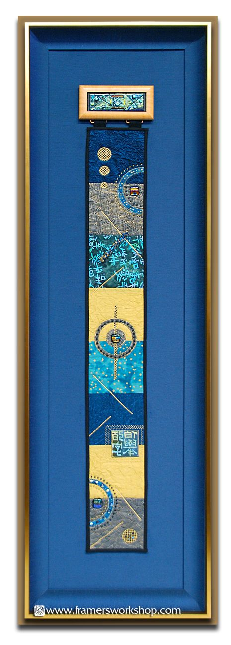 This large quilted scroll with glasswork elements was framed with a dark teal blue liner and matching background and surrounded with a dramatic Larson-Juhl frame. The project was finished with ultraviolet protective acrylic.