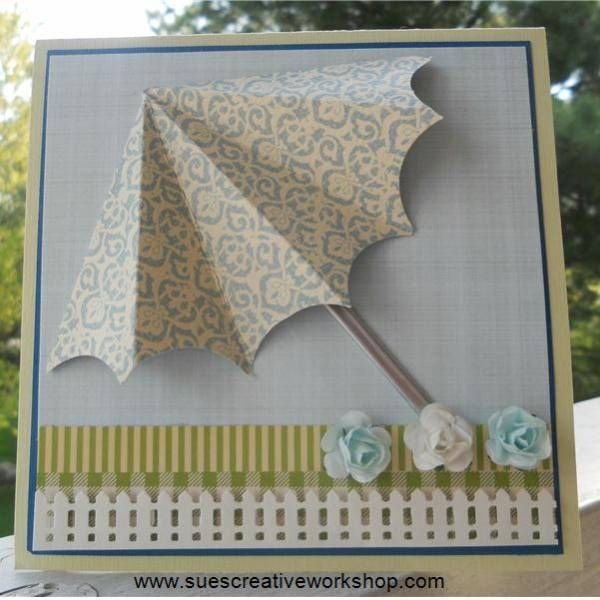 """1. Cut a 6"""" circle in half. Fold the half circle in half and then half again. 2. Fold each one of those sections in half. 3. Using a small circle punch, cut a small scallop out of each section. 4. Paint a coffee stirer with a silver paint pen. 5. Put together background layers. (5"""" x 5"""") Adhere to a 5 1/2"""" x 5 1/2"""" card. 6. Fold back the end two sections of the umbrella, trim as needed and adhere to front of card. 7. Apply a little bit of glue to the back of the silver stick and glue under"""