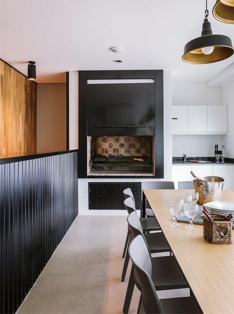 Cocina de un triplex con kitchenette. Los muebles son de melamina blanca laqueada (Domi) y la mesada es de mármol negro Brasil (Marmolería Mori). Una puerta guillotina en hierro negro guarda una parrilla.