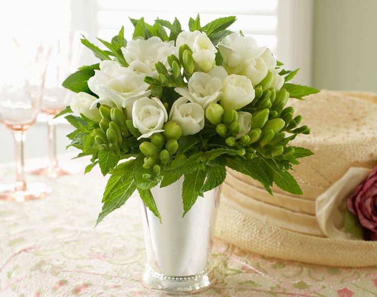 Petite floral arrangements made in silver julep cups can add an elegant touch and sparkle to a table or nightstand. Use fresh mint as the greenery and arrange with a few red roses. You can use these julep cup arrangements to decorate your table, either placing one at each guest's place setting, or arranging them as centerpieces. At the end of the party give one to each guest as they leave and thank them for joining in the fun!