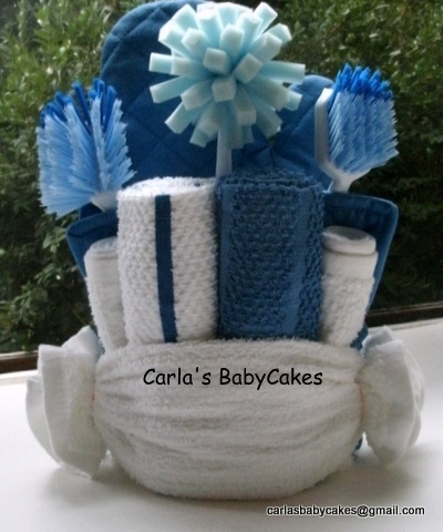 Kitchen towel cake with cleaning tools.  Contents:  2 dish towels, 4 dish cloths, 2 pot holders, 1 oven mitt, 2 brushes, 1 dish sponge, 2 scourers, 8 vinyl gloves and hand lotion sample.  Cost: $35.00, $35