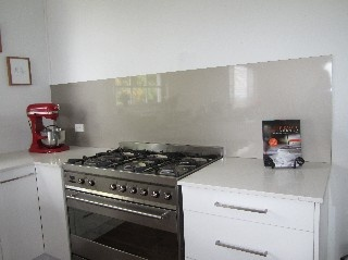 """This """"SMOKED SILVER PERLE"""" is one of the lovely Metaline kitchen splashback colours that fit in with almost any interior décor. A couple of simple contrasting items such as displayed in this kitchen brightens a corner while leaving a great clean working space that is easy to maintain."""