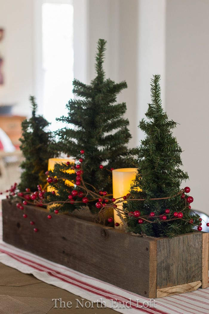 Small faux Christmas trees and pillar battery candles wrapped with red grapevine berries in a rustic wooden box.