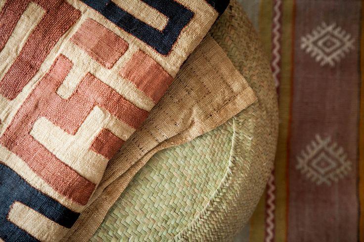 Curate your Space > Amatuli Kuba cloth on a grass pouf on a Turkish kilim
