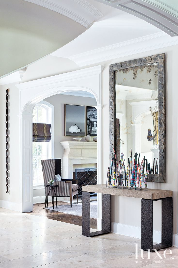 Metal Foyer Table Mirror : A console table in the foyer sits underneath an antiqued
